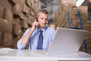 Warehouse manager using mobile phone and laptop at desk